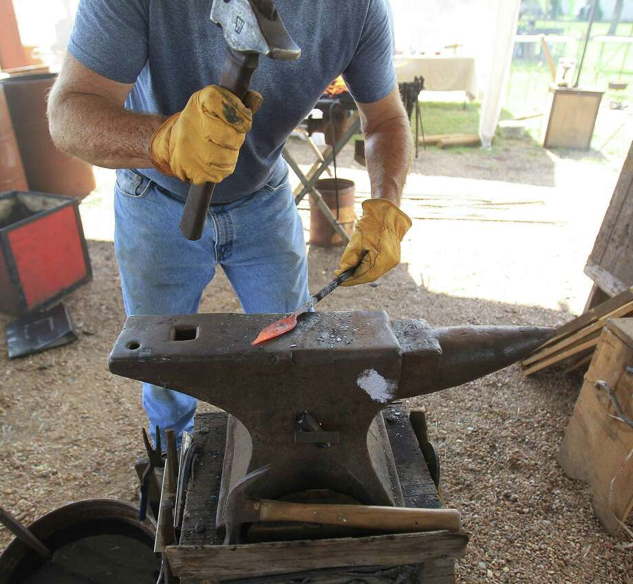 "David Koenig makes a leaf out of a piece of metal, pounding the shape out on an anvil as internationally acclaimed Virginia blacksmith/iron smelter Lee Sauder was demonstrating how to build a ""bloom iron"" furnace in which he will produce iron as the ancient people did, in Oldenburg, which is near La Grange, Wednesday,Oct. 2, 2013, in Oldenburg. Photo: Karen Warren, Houston Chronicle / © 2013 Houston Chronicle"
