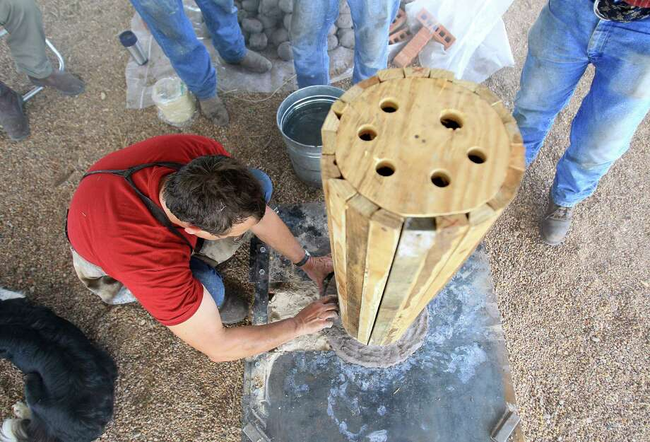 "Internationally acclaimed Virginia blacksmith/iron smelter Lee Sauder places clay around a wooden core, as he began building a ""bloom iron"" furnace in which he will produce iron as the ancients did in Oldenburg, which is near La Grange, Wednesday,Oct. 2, 2013, in Oldenburg. Photo: Karen Warren, Houston Chronicle / © 2013 Houston Chronicle"