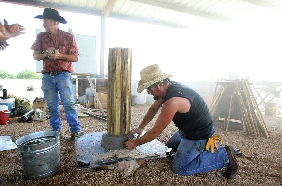 "Internationally acclaimed Virginia blacksmith/iron smelter Lee Sauder places clay around a wooden core, as he helps to build a ""bloom iron"" furnace as internationally acclaimed Virginia blacksmith/iron smelter Lee Sauder demonstrates the process in Oldenburg, which is near La Grange, Wednesday,Oct. 2, 2013, in Oldenburg. They are building the furnace to produce  iron as the ancient people did hundreds of years ago. Photo: Karen Warren, Houston Chronicle / © 2013 Houston Chronicle"