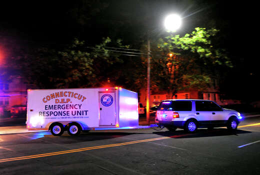 Connecticut DEP Emergency Response Unit arrives at the Woodside Green Condominiums on Summer Street in Stamford, Conn. on Thursday October 3, 2013. A woman who was killed by Washington DC police earlier in the day lived in one of the condos. Photo: Christian Abraham / Connecticut Post