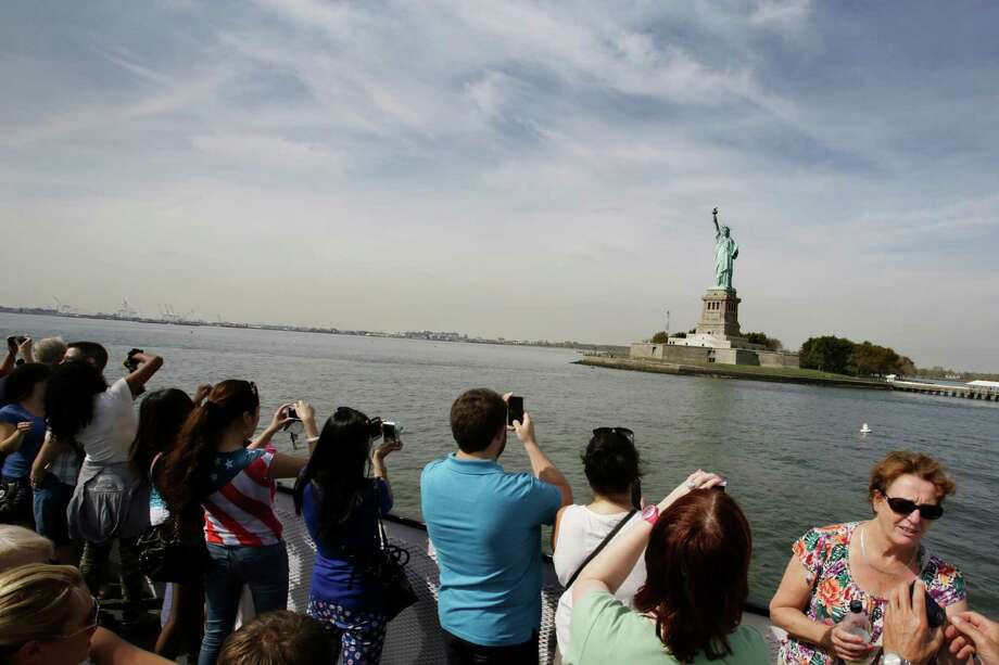 Tourists take photos of the Statue of Liberty while riding a tour boat in New York Harbor, Thursday, Oct. 3, 2013. The statue is administered by the National Park Service and is closed as a result of the government shutdown. President Barack Obama laid the blame for the government's partial shutdown at the feet of House Speaker John Boehner on Thursday, escalating a confrontation that is running the risk of a potentially damaging clash over the nation's borrowing authority. (AP Photo/Mark Lennihan) ORG XMIT: NYML102 Photo: Mark Lennihan / AP
