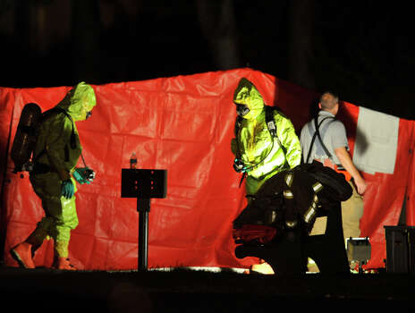 Stamford firefighters in HazMat suits work at Woodside Green Condominiums on Summer Street in Stamford, Conn., on Thursday, Oct. 3, 2013 in response to the shooting of a Stamford woman who tried to drive through a gate at the White House in Washington, D.C. earlier in the day. Photo: Jason Rearick / Stamford Advocate