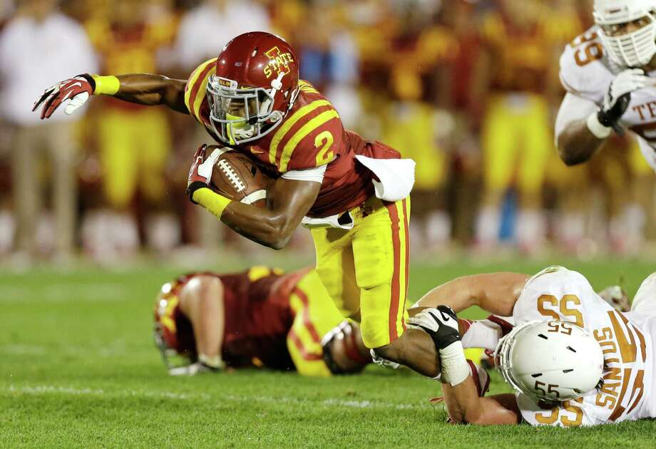 Iowa State running Aaron Wimberly (2) is tripped up by Texas linebacker Dalton Santos (55) during the first half of an NCAA college football game, Thursday, Oct. 3, 2013, in Ames, Iowa. Photo: Charlie Neibergall, Associated Press / AP