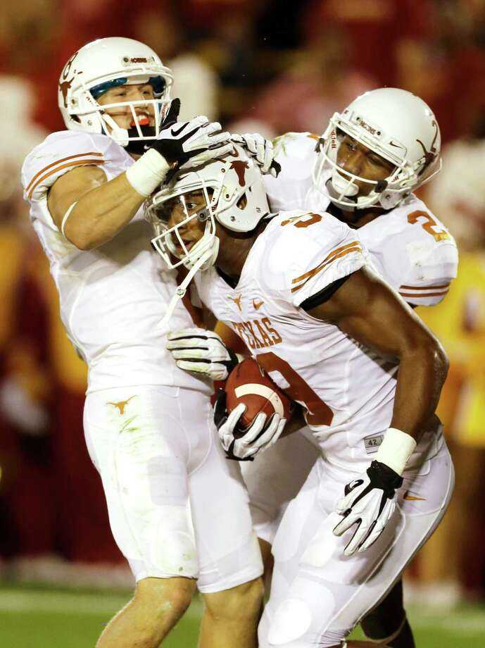Texas tight end John Harris (9) celebrates with teammates Jaxon Shipley, left, and Kendall Sanders, right, after catching a 44-yard touchdown pass during the first half of an NCAA college football game against Iowa State, Thursday, Oct. 3, 2013, in Ames, Iowa. Photo: Charlie Neibergall, Associated Press / AP