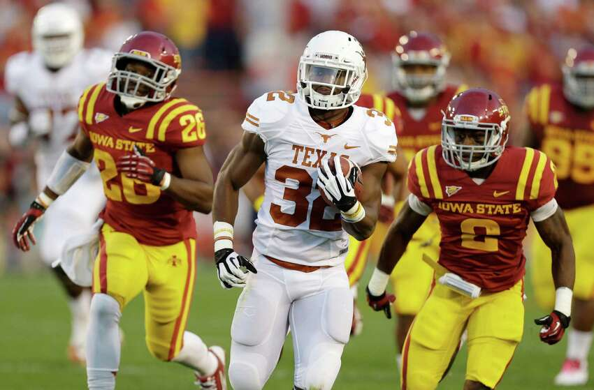 Texas running back Johnathan Gray, center, runs from Iowa State's Deon Broomfield, left, and Jansen Watson, right, during a 45-yard touchdown run in the first half of an NCAA college football game, Thursday, Oct. 3, 2013, in Ames, Iowa.