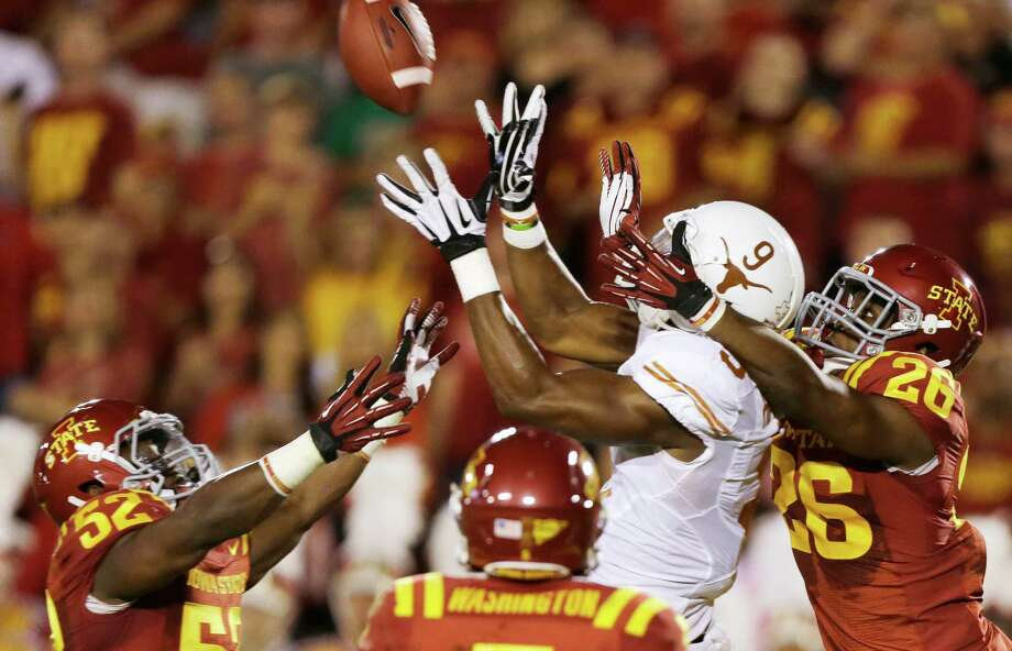 Texas tight end John Harris (9) catches a 44-yard touchdown pass over Iowa State's Jeremiah George (52) and Deon Broomfield (26) during the first half of an NCAA college football game on Thursday, Oct. 3, 2013, in Ames, Iowa. Photo: Charlie Neibergall, Associated Press / AP