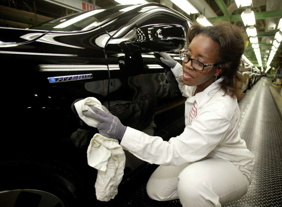 A worker touches up a 2014 Accord Hybrid as it is prepared to go out the factory doors. Honda says its new hybrid gets an estimated 50 miles per gallon. Photo: COURTESY / COURTESY OF HONDA
