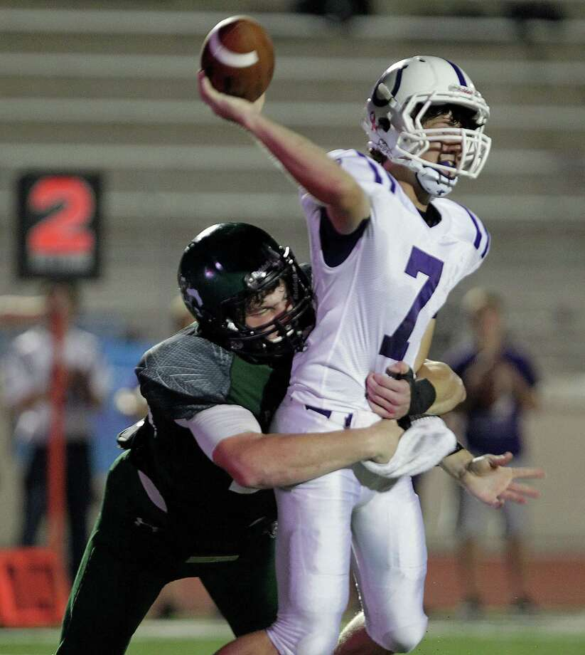 Kingwood's Michael Andrews left, forces Dayton quarterback Triston Baughman to dump the ball during the second quarter of high school football game action at Humble ISD's Turner Stadium Thursday, Oct. 3, 2013, in Humble. Photo: James Nielsen, Houston Chronicle / © 2013  Houston Chronicle