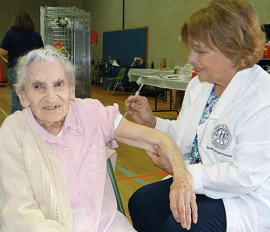 Nurse Janet Haringa administers a flu shot to 105-year-old Lenora Cox of Fairfield at a town flu inoculation clinic at the Fairfield Senior Center. Photo: Mike Lauterborn / Fairfield Citizen contributed