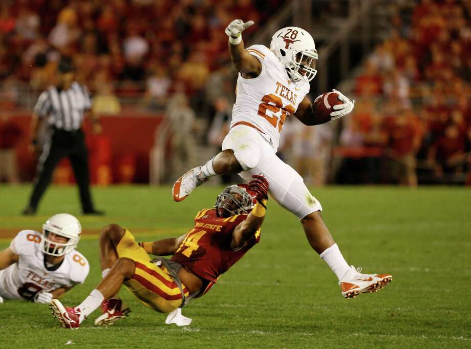 Running back Malcolm Brown #28 of the Texas Longhorns jumps over linebacker Jared Brackens #14 of the Iowa State Cyclones as he rushes for yards in the first half of play at Jack Trice Stadium on October 3, 2013 in Ames, Iowa. Photo: David Purdy, Getty Images / 2013 Getty Images