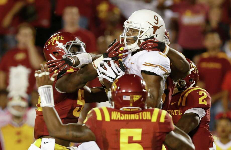 Tight end John Harris #9 of the Texas Longhorns pulls in a reception for a touchdown in the end zone as defensive back Jacques Washington #5, linebacker Jeremiah George #52, defensive back Deon Broomfield #26 and defensive back Jansen Watson #2 of the Iowa State Cyclones defend in the first half of play at Jack Trice Stadium on October 3, 2013 in Ames, Iowa. Photo: David Purdy, Getty Images / 2013 Getty Images