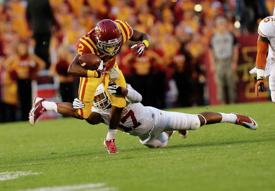 Running back Aaron Wimberly #2 of the Iowa State Cyclones is tackled by safety Adrian Phillips #17 of the Texas Longhorns in the first half of play at Jack Trice Stadium on October 3, 2013 in Ames, Iowa. Photo: David Purdy, Getty Images / 2013 Getty Images