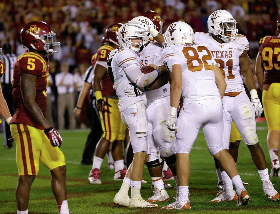 Texas quarterback Case McCoy, center, celebrates with teammates after scoring a touchdown during the second half of an NCAA college football game against Iowa State, Thursday, Oct. 3, 2013, in Ames, Iowa. Texas won 31-30. Photo: Charlie Neibergall, Associated Press / AP