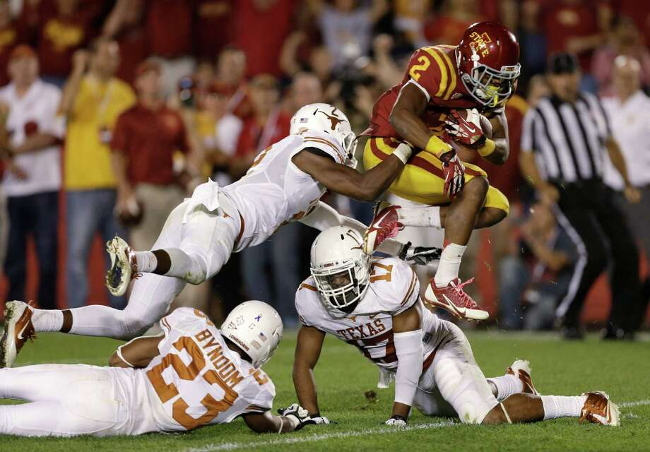 Iowa State running back Aaron Wimberly, right, leaps past Texas defenders Carrington Byndom (23), Mykkele Thompson and Adrian Phillips (17) during a 20-yard touchdown run in the second half of an NCAA college football game, Thursday, Oct. 3, 2013, in Ames, Iowa. Texas won 31-30. Photo: Charlie Neibergall, Associated Press / AP