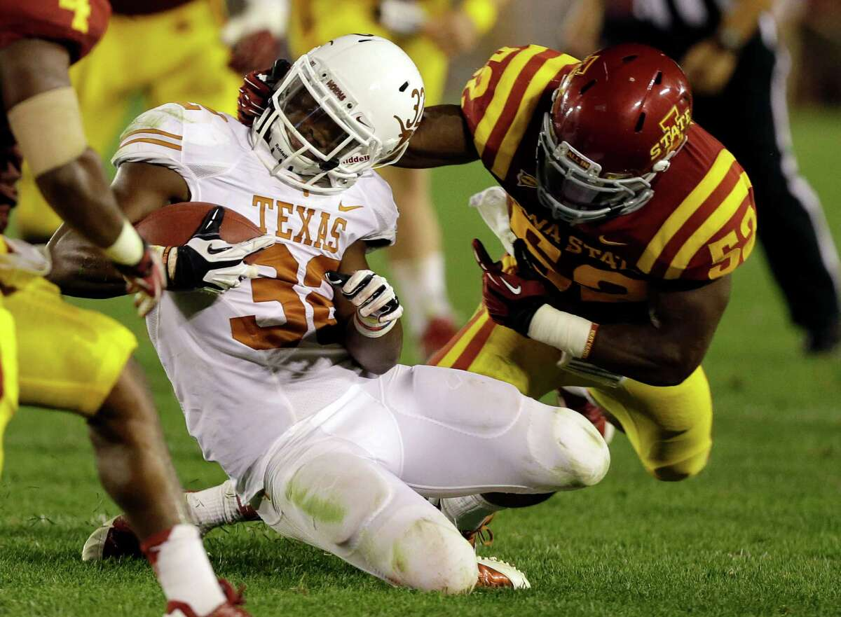 Texas running back Johnathan Gray is tackled by Iowa State linebacker Jeremiah George, right, during the second half of an NCAA college football game on Thursday, Oct. 3, 2013, in Ames, Iowa. Texas won 31-30.