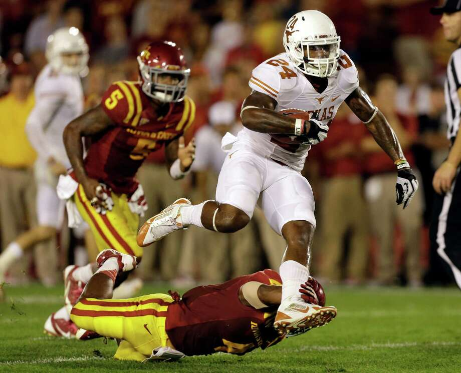 Texas running back Joe Bergeron (24) runs over Iowa State defensive back Sam E. Richardson during the second half of an NCAA college football game on Thursday, Oct. 3, 2013, in Ames, Iowa. Texas won 31-30. Photo: Charlie Neibergall, Associated Press / AP