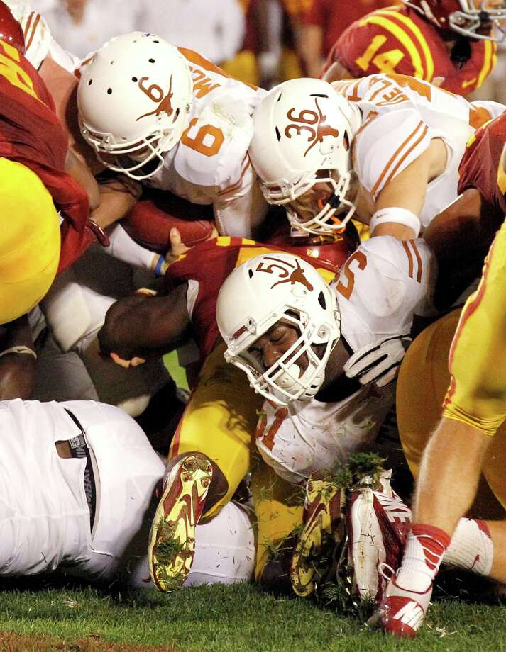 Quarterback Case McCoy #6 of the Texas Longhorns drives the ball across the goal line to score with the help of offensive tackle Donald Hawkins #51 and defensive back Dillon Boldt #36 late in the second half of play at Jack Trice Stadium on October 3, 2013 in Ames, Iowa. Texas defeated Iowa State 31-30. Photo: David Purdy, Getty Images / 2013 Getty Images