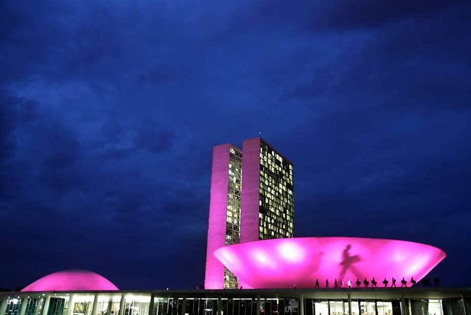 Congress is illuminated in pink in honor of Breast Cancer Awareness month in Brasilia, Brazil, Wednesday, Oct. 2, 2013. The shadow on the building is from a soldier patrolling outside the lower house. (AP Photo/Eraldo Peres) Photo: Eraldo Peres, Associated Press