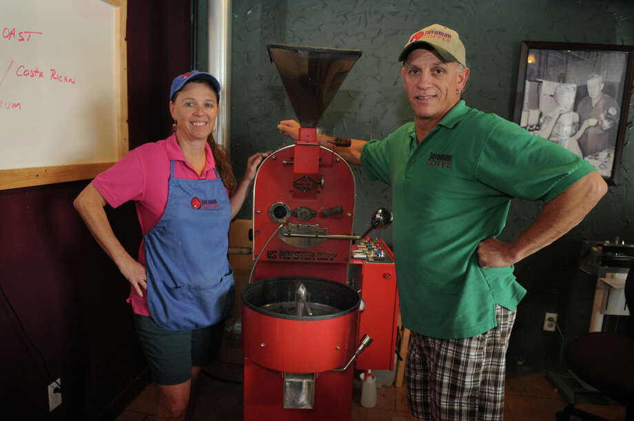 Mark Norelli, from right, and his wife, Melanie, show off their coffee roaster at Javaman Coffee in Humble. Photo: Jerry Baker, Freelance