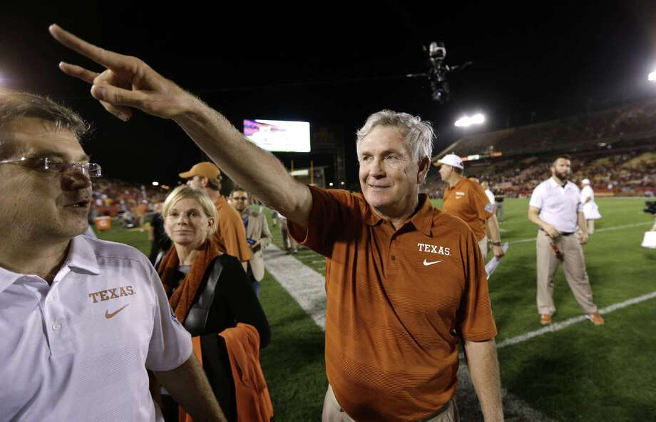 """Mack Brown flashes the """"Hook 'em Horns"""" after his team escaped Ames with a win."""