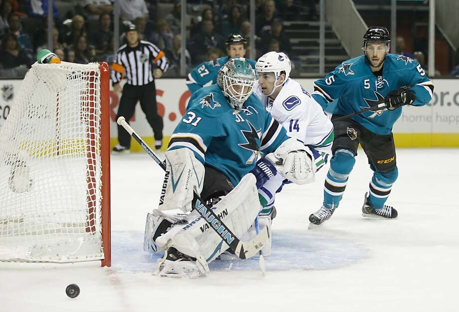 Sharks goalie Antti Niemi (31) thwarts a scoring attempt by Vancouver's Alex Burrows. Photo: Ezra Shaw, Getty Images