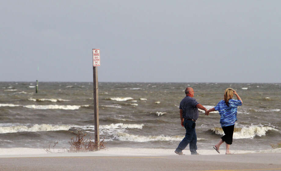 A couple walks along the beach on Thursday, Oct. 3, 2013, in Gulfport, Miss. Preparations are underway along the Mississippi Gulf Coast as Tropical Storm Karen moves through the Gulf of Mexico. Photo: The Sun Herald, Amanda McCoy
