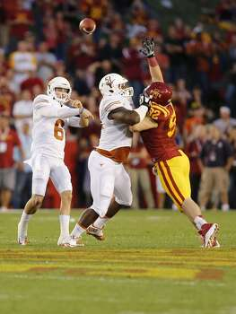 Quarterback Case McCoy #6 of the Longhorns throws under pressure from defensive lineman Austin Krick #92 of the Cyclones as offensive tackle Donald Hawkins #51 of the Longhorns blocks. Photo: David Purdy, Getty Images