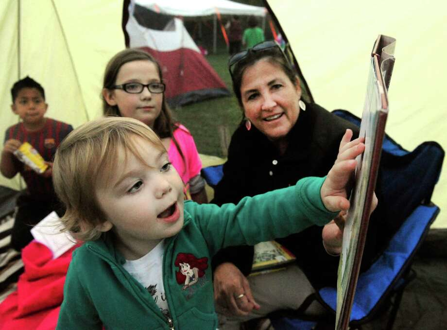 "Hailey Mott, 2, reacts to 'fractured fairy tales' read by Suzanne Galante, right, as students and their siblings listen to storytelling during ""The Reading Campout,"" at the Johnson School, in Bethel, Conn. Thursday, Oct. 3, 2013. Photo: Michael Duffy / The News-Times"
