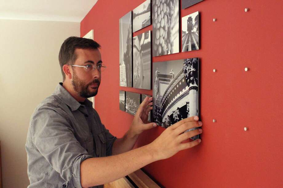 Jason Rodman installs a display of his photography using a Collagewall template. Photo: Associated Press