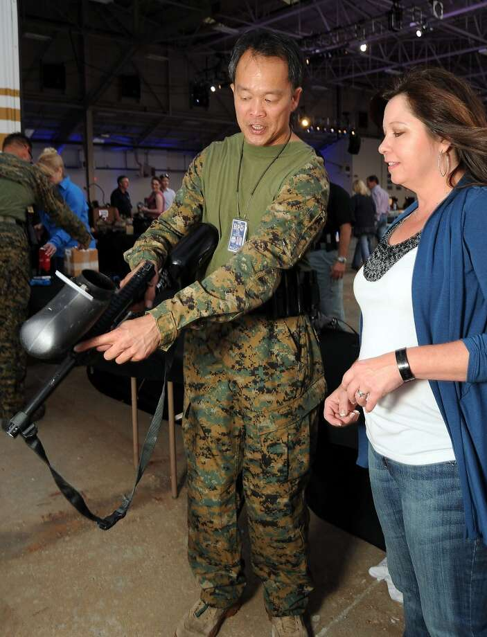 Sherry Self gets a lesson on the pepper ball gun from HPD SWAT sniper Edwin Lem at the HPD True Blue Gala benefitting the Houston Police Foundation at the Landry's Flight Hanger at Hobby Airport Saturday Oct. 20,2012. Photo: Dave Rossman, For The Houston Chronicle