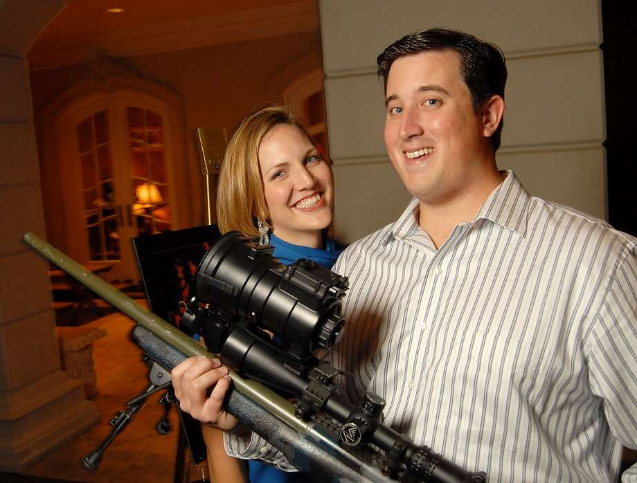 Josh and Tracy Popes with one of the SWAT teams sniper rifles at the Second Annual True Blue Gala sponsored by the Houston Police Foundation at the home of Paige and Tilman Fertitta Saturday Oct. 17,2009. Photo: Dave Rossman, For The Chronicle
