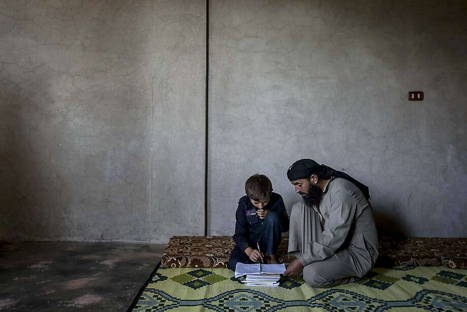 Young boys attend class at the public school in Madaya, Syria. Right: Ahmed al-Fikri helps his 12-year-old son Abdo al-Fikri, with his homework. Photo: Uncredited, Associated Press