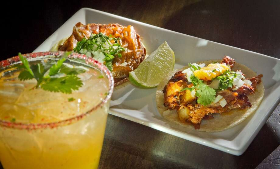 A Taco al Pastor and a Taco el Califa with Hacienda de Chihuahua cocktail at Mosto Bar. Photo: John Storey, Special To The Chronicle