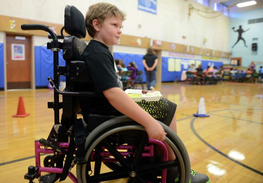 Cody Cairns, a fourth grade student at Tashua School in Trumbull, Conn., tries to maneuver a wheel chair while carrying a lunch tray to get a sense of the challenges a student with gross motor impairment faces Friday, Oct. 4, 2013 during the school's annual Sensitivity Day. Photo: Autumn Driscoll / Connecticut Post