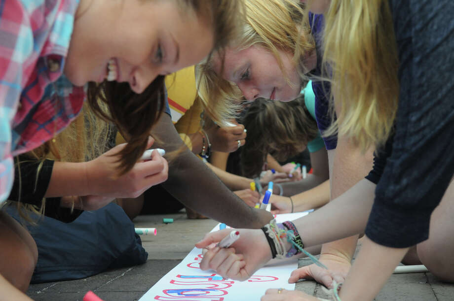 GHS student Elizabeth Fawcett, left, and SHS Margaret Simpson, right, sign banners together as students from Brien McMahon, Stamford and Greenwich High Schools joined forces in a Bullying Awareness Walk which ended with a banner signing at Greenwich High School in Greenwich, Conn., October 4, 2013. Sixteen McMahon and Stamford students were greeted by their peers at Greenwich High after making the trek from Stamford High to Greenwich. The two groups exchanged banners and illustrated them together in a commitment to battle bullying. Photo: Keelin Daly / Stamford Advocate Freelance