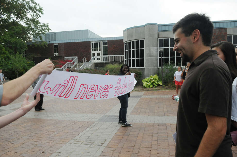 Elias Frank, right, a senior at Greenwich High and founder of GHS Connections, watches as  Phenderine Lyra unfruls a banner gift to he and fellow students from Brien McMahon and Stamford High School students as they all join forces in a Bullying Awareness Walk which ended with a banner signing at Greenwich High School in Greenwich, Conn., October 4, 2013. Sixteen McMahon and Stamford students were greeted by their peers at Greenwich High after making the trek from Stamford High to Greenwich. The two groups exchanged banners and illustrated them together in a commitment to battle bullying. Photo: Keelin Daly / Stamford Advocate Freelance