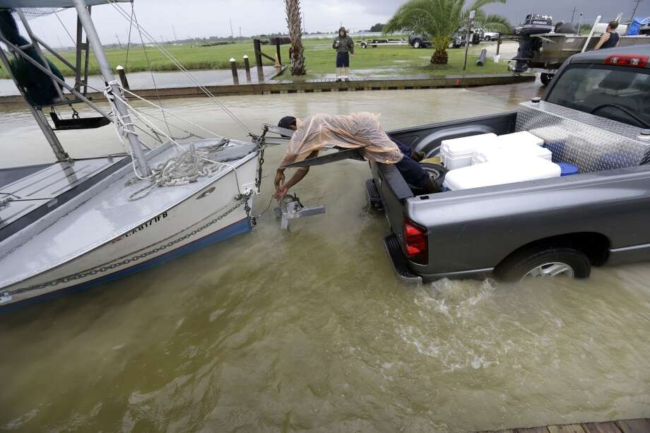 C.J. Johnson pulls a shrimp boat out of the water, in anticipation of Tropical Storm Karen, at Myrtle Grove Marina in Plaquemines Parish, La., Friday, Oct. 4, 2013.  National Hurricane Center forecasters expect Karen to be near the central Gulf Coast on Saturday as a weak hurricane or tropical storm. Along with strong winds, the storm was expected to produce rainfall of 3 to 6 inches through Sunday night, with isolated totals up to 10 inches possible. Forecast tracks showed it possibly brushing, or crossing, the southeast Louisiana coast before veering eastward toward south Alabama and the Florida panhandle. Photo: Gerald Herbert, Associated Press