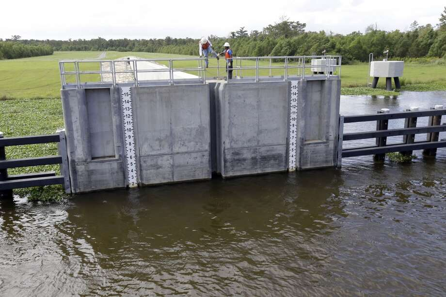 Workers prepare to lower a flood gate into Hero Canal, as part of the hurricane protection system protecting the greater New Orleans area, in anticipation of Tropical Storm Karen, in Belle Chasse, La., Friday, Oct. 4, 2013. Photo: Gerald Herbert, Associated Press