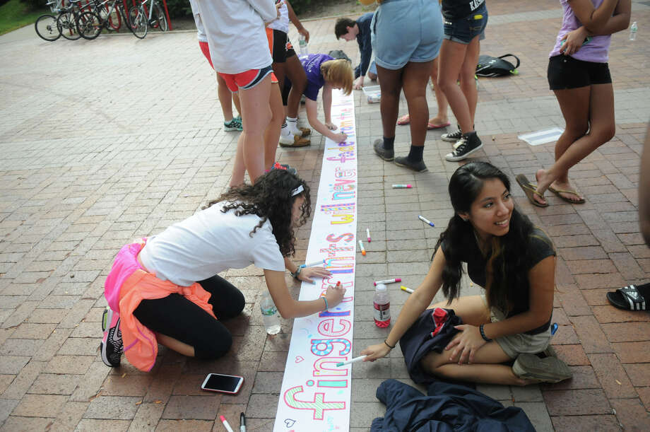 SHS students Marcela Alzate, left, and Brianna Samaranayake sign a banner as students from Brien McMahon, Stamford and Greenwich High Schools joined forces in a Bullying Awareness Walk which ended with a banner signing at Greenwich High School in Greenwich, Conn., October 4, 2013. Sixteen McMahon and Stamford students were greeted by their peers at Greenwich High after making the trek from Stamford High to Greenwich. The two groups exchanged banners and illustrated them together in a commitment to battle bullying. Photo: Keelin Daly / Stamford Advocate Freelance
