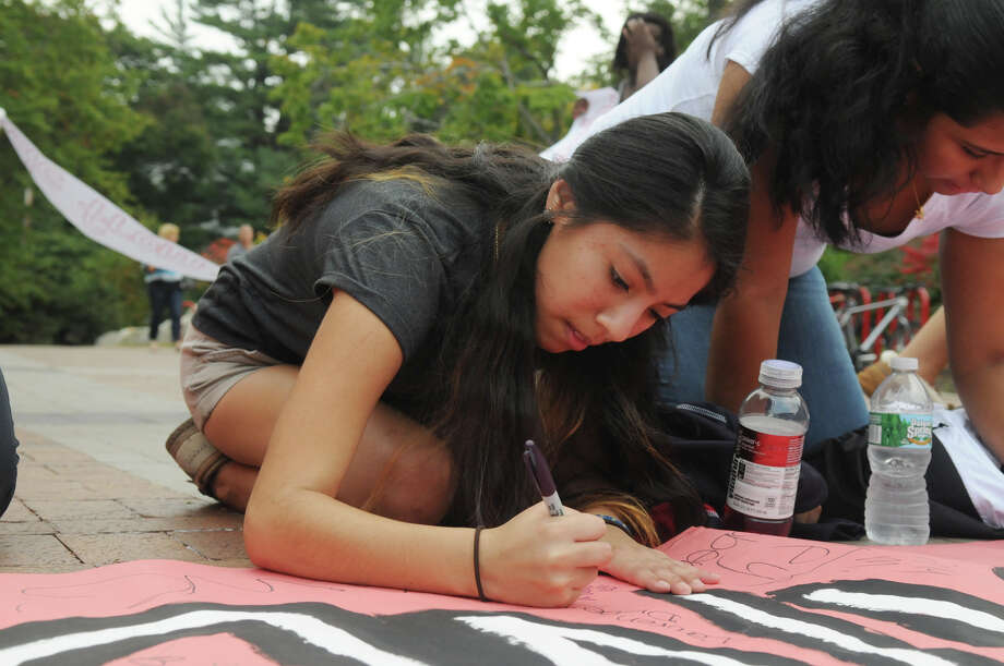 Brianna Samaranayake signs a banner as she and students from Brien McMahon, Stamford and Greenwich High Schools joined forces in a Bullying Awareness Walk which ended with a banner signing at Greenwich High School in Greenwich, Conn., October 4, 2013. Sixteen McMahon and Stamford students were greeted by their peers at Greenwich High after making the trek from Stamford High to Greenwich. The two groups exchanged banners and illustrated them together in a commitment to battle bullying. Photo: Keelin Daly / Stamford Advocate Freelance