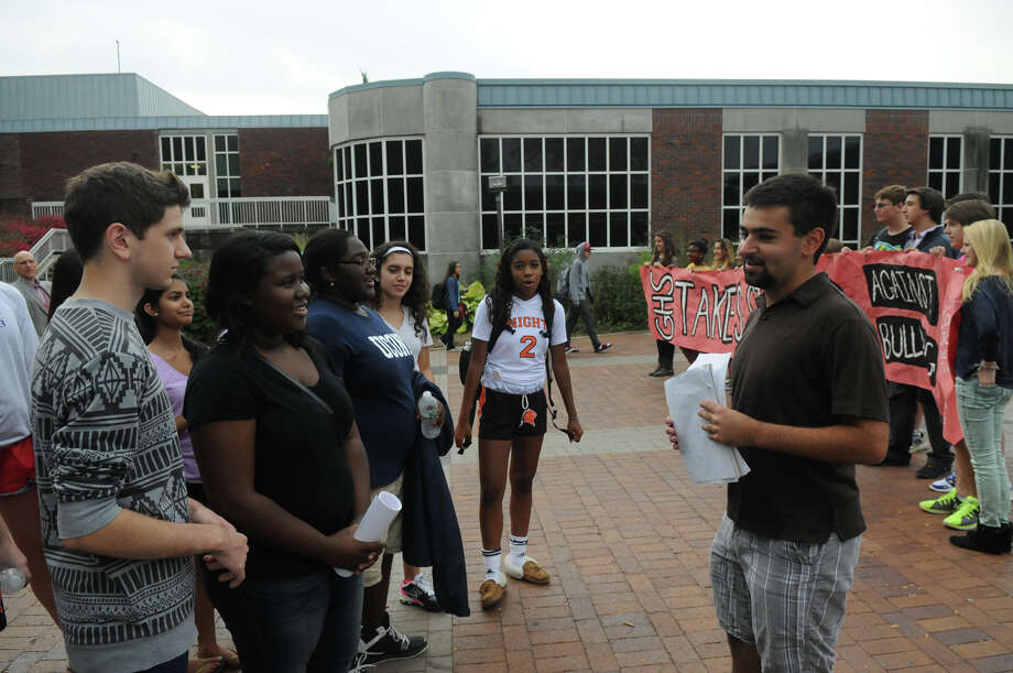 Elias Frank, right, a senior at Greenwich High and founder of GHS Connections, welcomes students from Brien McMahon and Stamford High Schools including Nic Solano, left, and Phenderine Lyra as the students joined forces in a Bullying Awareness Walk which ended with a banner signing at Greenwich High School in Greenwich, Conn., October 4, 2013. Sixteen McMahon and Stamford students were greeted by their peers at Greenwich High after making the trek from Stamford High to Greenwich. The two groups exchanged banners and illustrated them together in a commitment to battle bullying. Photo: Keelin Daly / Stamford Advocate Freelance