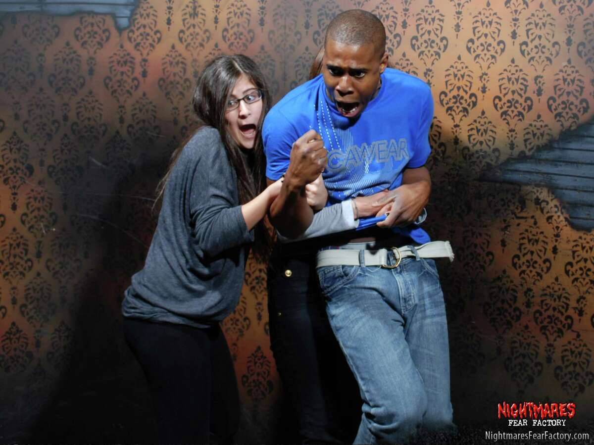 Guests at the Nightmares Fear Factory in Niagara Falls, Canada show shock and surprise in the haunted house in 2013.