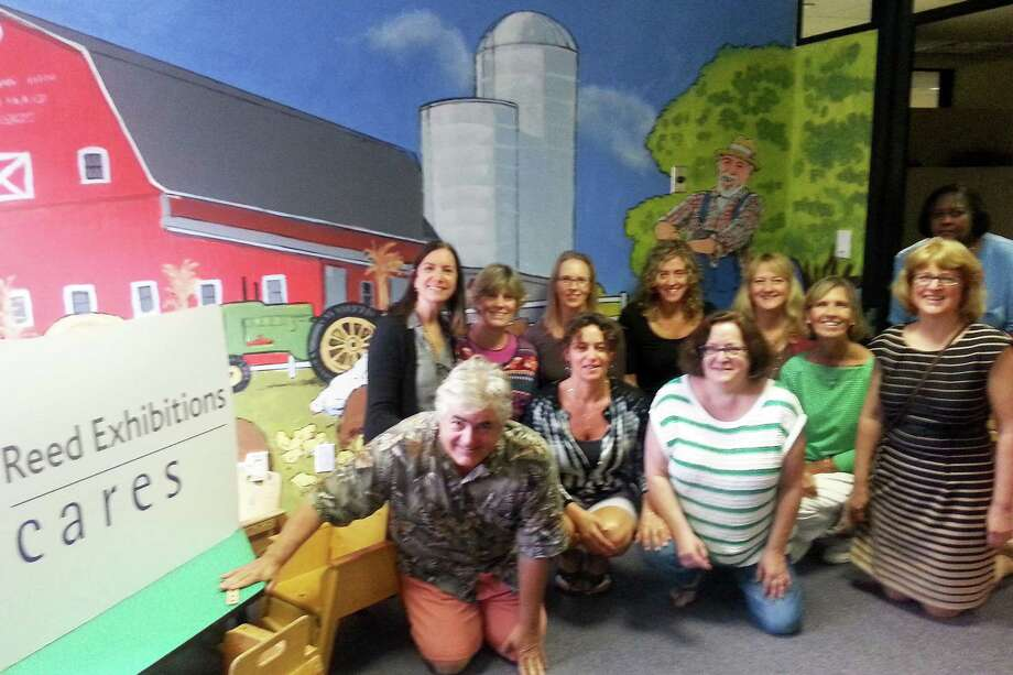 Staffers from the STAR Rubino Family Center pose in front of Old McDonald mural recently painted at the center by volunteers from Reed Exhibitions. Photo: Contributed Photo / Norwalk Citizen contributed