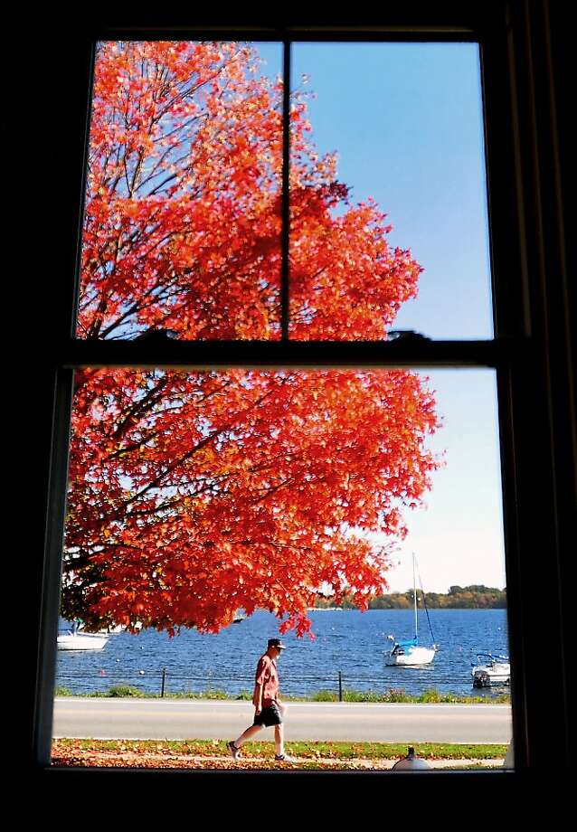 Peak color in upstate New York: A man strolls along Lake Street in Rouses Point. Photo: Rob Fountain, Associated Press