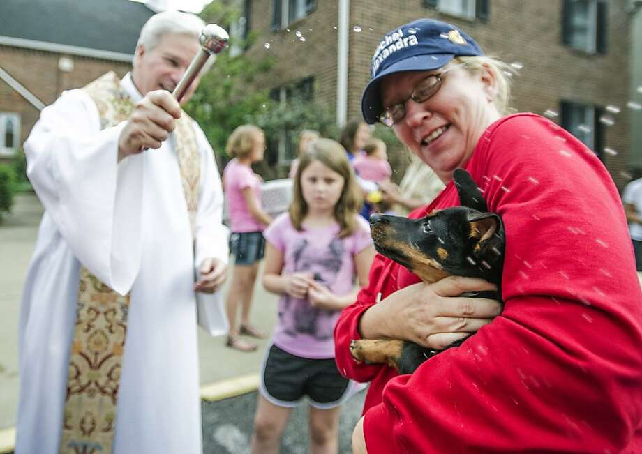 NO! He turned me into a dog! Actual AP caption: Marie Lammy holds her goat Penelope to receive a blessing from