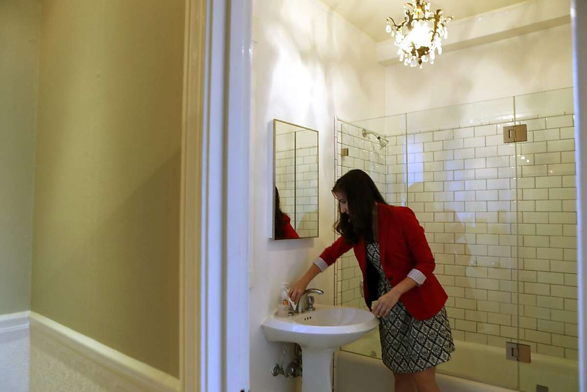 Cristina Bravo Olmo wipes down her bathroom before going to work so the home can be shown to prospective buyers on Friday October 4, 2013 in San Francisco, Calif.