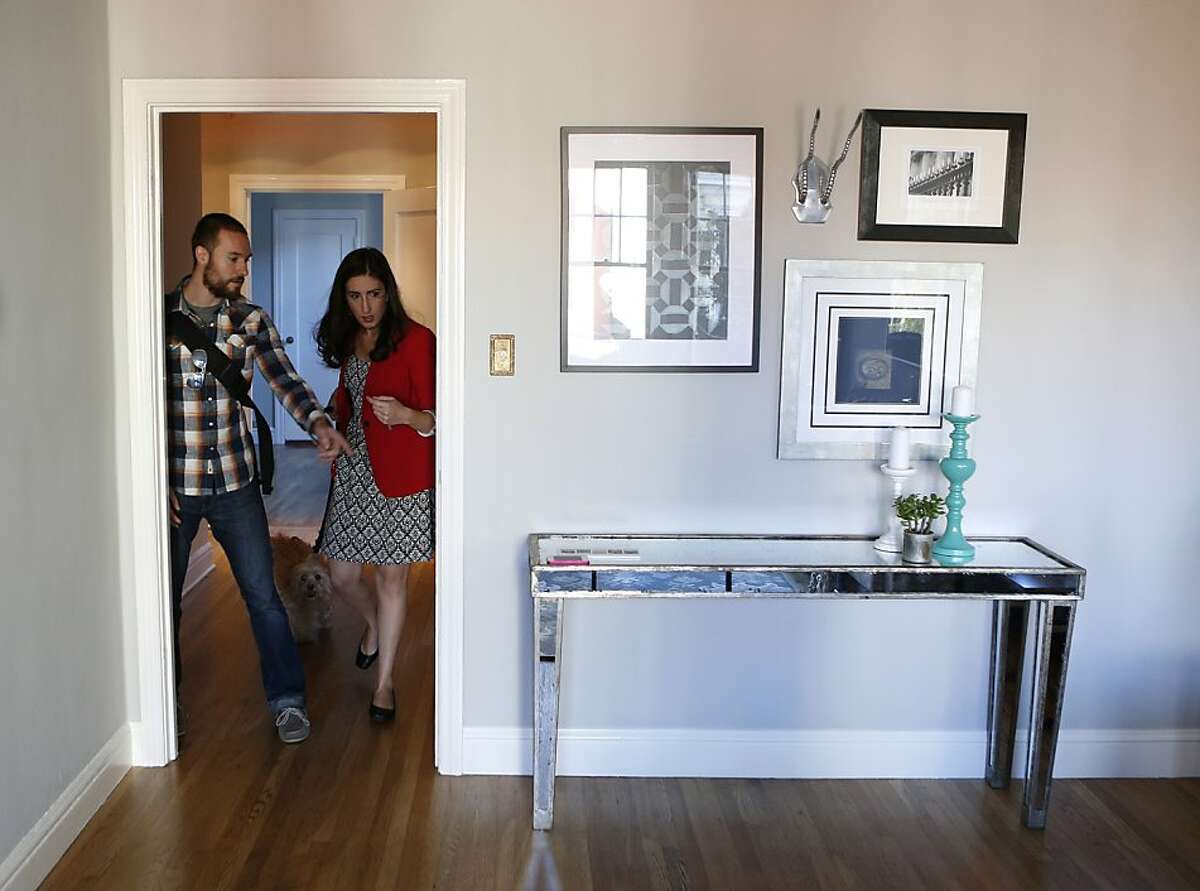 Cristina Bravo Olmo (right) and her boyfriend Brett McBee-Wise stage their condo before going to work so their home can be shown to prospective buyers on Friday October 4, 2013 in San Francisco, Calif.