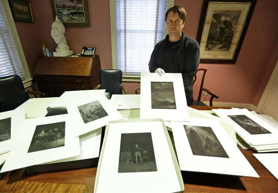"In this Friday, Sept. 27, 2013 photo, Chris Semtner, curator of the Edgar Allan Poe Museum, displays illustrations that they hope to preserve and publish at the museum in Richmond, Va. The museum is hoping to raise $60,000 to preserve and publish 43 illustrations of Poe's ""The Raven,"" done by James Carling in the 1880s. (AP Photo/Steve Helber) Photo: Steve Helber, STF / AP"