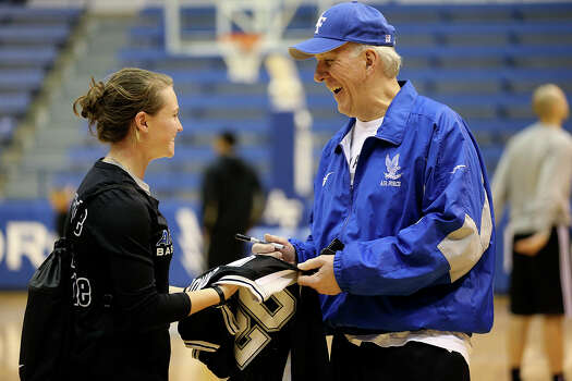 San Antonio Spurs Head Coach Gregg Popovich signs an autograph for U.S. Air Force Women's Basketball guard Izzie Englehart, 18, after a light team workout on their last day at the United State Air Force Academy in Colorado Springs, Colorado, Friday, Oct. 4, 2013. Photo: Jerry Lara, San Antonio Express-News / ©2013 San Antonio Express-News