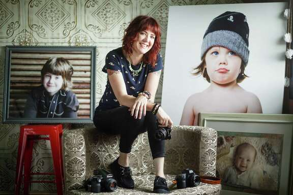 """Local photographer Farrah Braniff is surrounded in her studio by images she has taken of her three children. Braniff is the author of """"Moments That Matter."""""""
